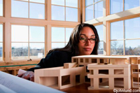 Female architect examining the model of the building she has designed.  The architect is an attractive ethnic woman with long dark hair and she is wearing eye glasses.